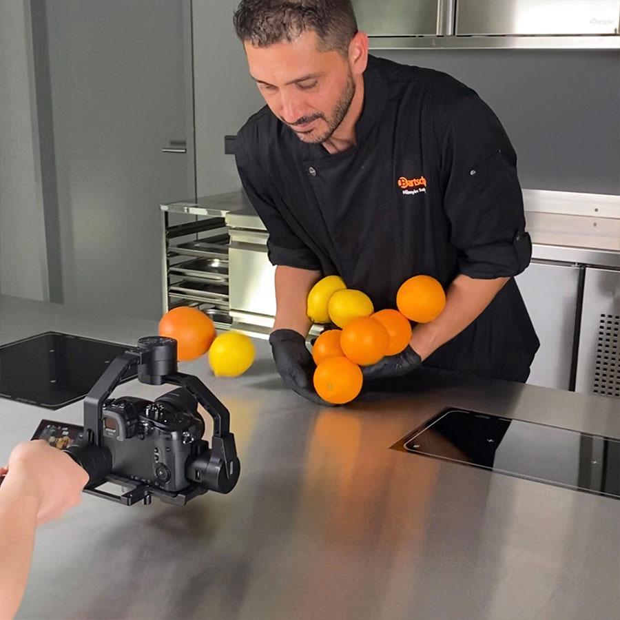 Video-Aufnahmen mit einem Koch der Obst über den Tisch rollen lässt